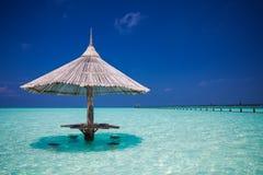 Bambustrandparaply med stångplatser i vattnet Royaltyfri Foto