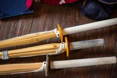 Bambusvärdnärbild Kendo handskar, hjälm och bambusvärd på en träyttersida royaltyfri foto
