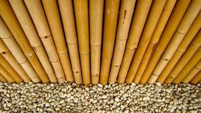 Bambuszaun mit Steinen Stockfoto