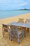 Bambutabell och stolar på sandstranden Royaltyfri Fotografi