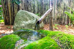 Bambuvattenspringbrunn med den mossiga bunken och att vagga arkivfoto