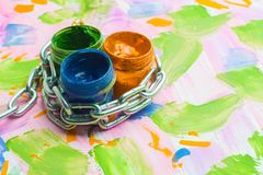 Ban on creativity, three cans of paint are entwined with a metal chain, a multicolored background royalty free stock image