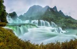 Ban Gioc Waterfall craggy limestone permissive side misty morning Stock Photo