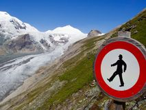 Sign in front of glacier big mountain in alps. Ban sign in front of glacier Royalty Free Stock Images