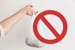 Ban single use plastic, stop sign. Woman holding in hand groceries in plastic polyethylene bag. Zero Waste shopping concept. Reuse, reduce, recycle, refuse stock images