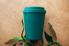 Ban single use plastic. Stylish reusable eco coffee cup and bamboo leaves on wooden background, flat lay. Cup from natural bamboo. Fiber, zero waste concept royalty free stock photos