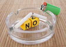 Ban smoking in public places. The word - no, or include the yellow cubes in clear glass ashtrays on gray background - concept ban smoking in public places and Royalty Free Stock Image