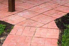 Bana av röda konkreta tegelplattor bland jordning Royaltyfri Fotografi