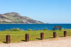 Bana, bänk, hav och ö Helig ö, Lamlash, Arran, Scotl arkivbild