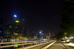 Bana med kommersiella byggnader som ses under nigh tid i Marina Bay arkivbilder
