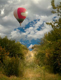Bana till himmel-enballongen som flyger över skogen och en bana i en busksnår av träd Arkivbilder