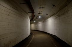 Bana till och med en mörk krökt välvd tunnel med ljusa väggar i en gammal övergiven byggnad arkivfoton