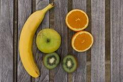 Banaan, appel, sinaasappelen en kiwien op een lijst Stock Foto's