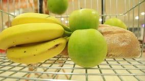 Banaan en appel in een mand in supermarkten stock videobeelden