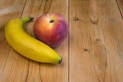 Banaan en perzik op hout Royalty-vrije Stock Afbeeldingen