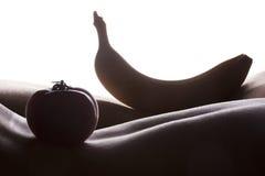 Banaan en tomaat op vrouwenhuid stock afbeeldingen
