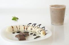 Banaan met chocoladebovenste laagje en milkshake en sierverlof Stock Afbeeldingen