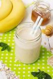 Banaan smoothies in een glaskruik op een witte achtergrond Stock Foto's