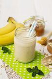 Banaan smoothies in een glaskruik op een witte achtergrond Stock Afbeelding