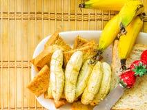 Banaantoost op Bruine broodplakken stock afbeeldingen