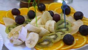 Banai apelsiner, druvor, kiwi skivade, närbilden Maträtt för ny frukt på en festlig äta middag tabell Blandade skivade fruktstekn stock video