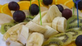 Banai apelsiner, druvor, kiwi skivade, n?rbilden Matr?tt f?r ny frukt p? en festlig ?ta middag tabell Blandade skivade fruktstekn stock video