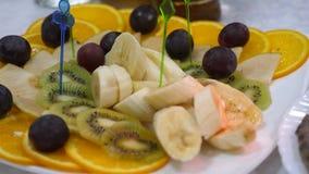 Banai, arance, uva, kiwi ha affettato, primo piano Alimento delizioso sulla tavola Piatto della frutta fresca ad un tavolo da pra archivi video