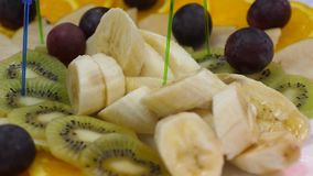 Banai, pomara?cze, winogrona, kiwi pokraja?, w g?r? ?wie?y owocowy naczynie przy ?wi?tecznym ?omota sto?em Asortowani pokrojeni o zbiory