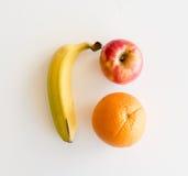 Banan, äpple och apelsin från över arkivbilder