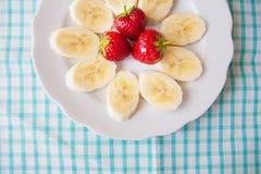 Banan i truskawki na białym talerzu i kolorowej pielusze zdjęcie stock