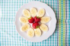 Banan i truskawki na białym talerzu i kolorowej pielusze obraz stock