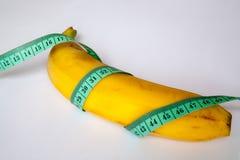 Banan med en linjal Royaltyfria Bilder
