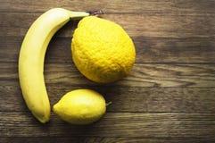 Banan och citroner på träbakgrunden, sund mat, hälsa Royaltyfri Bild