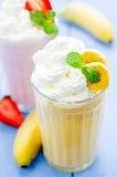 Banan- och jordgubbemilkshake med piskad kräm Arkivbilder