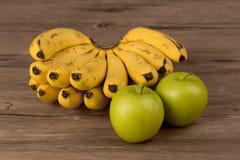Banan och äpple på trä Arkivbilder