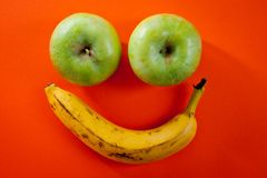 Banan och två äpplen som ligger i formen av en smiley på en ljus orange bakgrund arkivfoton
