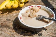 Banan w kokosowego mleka deserze umieszcza na starym drewnianym stołowym tle Obraz Stock