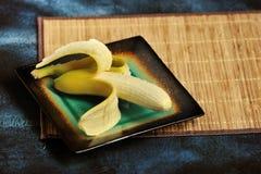 Banan z łupą odcinał na talerzu zdjęcia royalty free