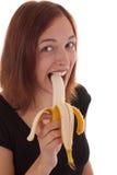 The banana. A young woman eating a banana stock photos