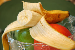 Banana. Half of a peeled banana on top of a green apple and a peach in the fruit bowl royalty free stock image