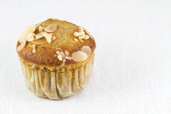 Banana almond muffin on white tablecloth. Sweet banana almond muffin on white tablecloth Stock Image