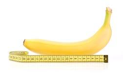 Banana amarela com fita de medição Fotos de Stock Royalty Free