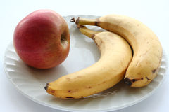 Banana and apple. Two banana and apple on large white tablemat Stock Image