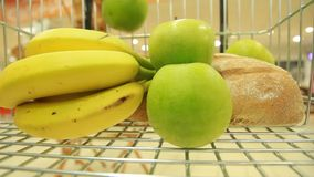 Banana and apple in a basket in supermarkets. Basket of products in supermarkets. shopping. basket with cheese bread stock video footage