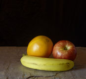 Banana With Apple And Orange On Slate. Banana propping up apple and orange, on gray slate, in front of black background Stock Images