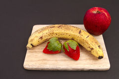 Banana apple and strawberries. On a cutting board Royalty Free Stock Images