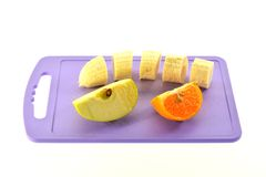 Banana Apple and Tangerine on the cutting board Stock Images