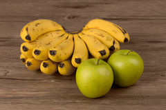 Banana and apple  on wooden Stock Images