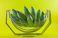 Green banana in basket on yellow background Royalty Free Stock Photography