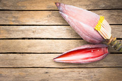 Banana blossom on wooden background.Raw food or background food. Stock Photos